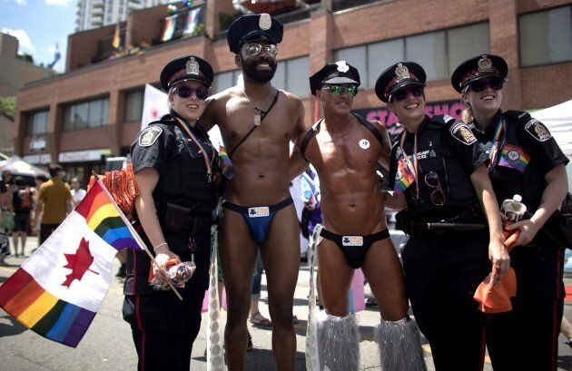 Revellers pose for a photos with police officers at the annual Pride Parade in Toronto on July 3,