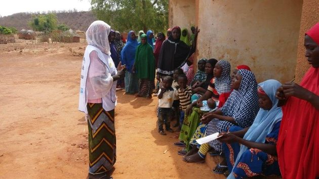 A community health worker in Niger speaks with a group of local women about the signs and symptoms of