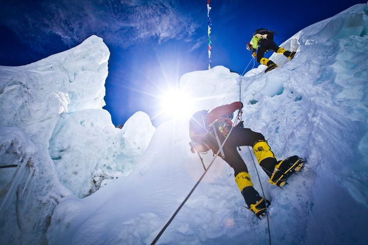 Two climbers scaling a vertical cliff in the Khumbu Icefall