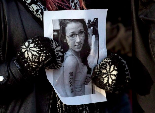 A woman holds a photo as several hundred people attend a community vigil to remember Rehtaeh Parsons at Victoria Park in Halifax on April 11, 2013.