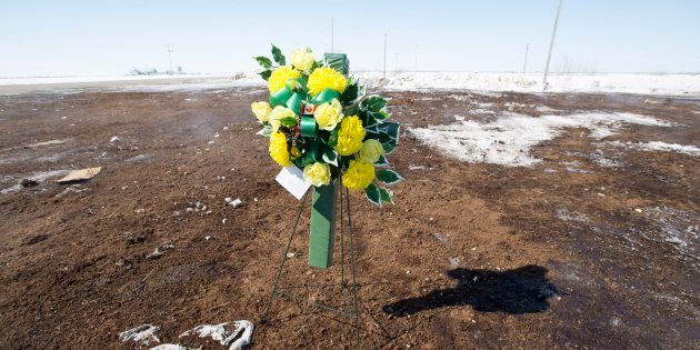 Flowers laid by RCMP officers sit at the intersection of a crash site near Tisdale, Sask. on April, 8,