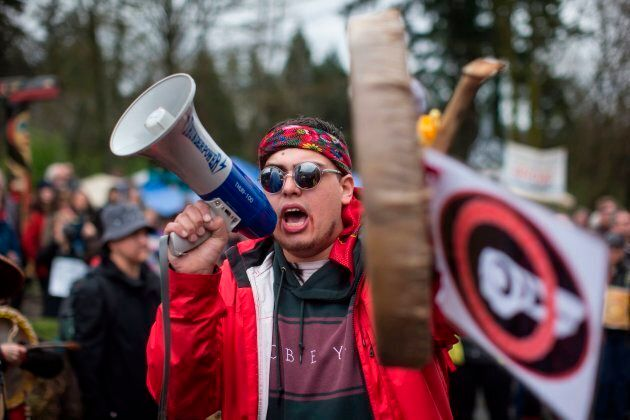 In this April 7, 2018 photo, Cedar George-Parker addresses the crowd as protesters opposed to the Kinder Morgan Trans Mountain pipeline extension defy a court order and block an entrance to the company's property, in Burnaby, B.C.