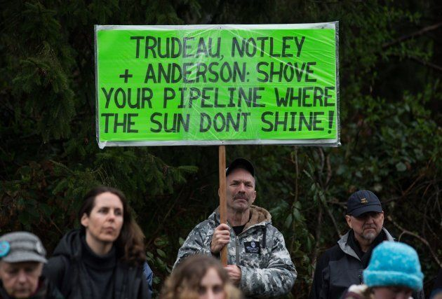 A man holds a sign while listening as other protesters opposed to the Kinder Morgan Trans Mountain pipeline extension defy a court order and block an entrance to the company's property, in Burnaby, B.C., on April 7, 2018.
