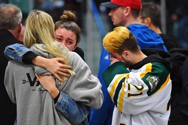 Mourners comfort each other as people attend a vigil at the Elgar Petersen Arena, home of the Humboldt...