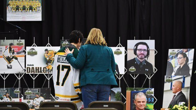 Mourners comfort each other as they look at photographs prior to a vigil at the Elgar Petersen Arena,...