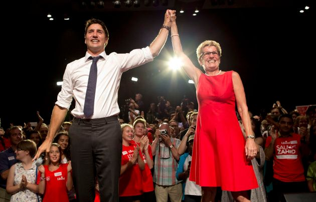 Ontario Premier Kathleen Wynne and then-Liberal Party leader Justin Trudeau join hands during an election...