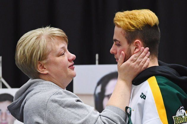 Humboldt Broncos player Nick Shumlanski, who was released from hospital Sunday, is comforted by a mourner...