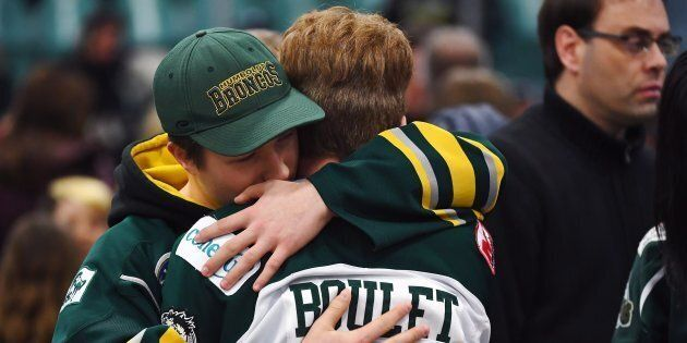 Mourners comfort each other during a vigil to honour the victims of a fatal bus accident in Humboldt, Sask. on Sunday.