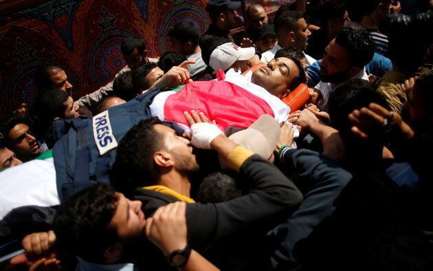 Colleagues of Palestinian journalist Yasser Murtaja, 31, who was killed by an Israeli sniper, carry his...