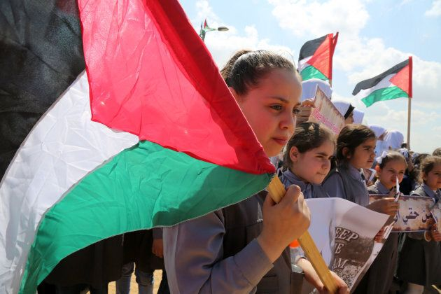 Palestinian students hold banners at the Israel-Gaza border in a tent city protest demanding the right...