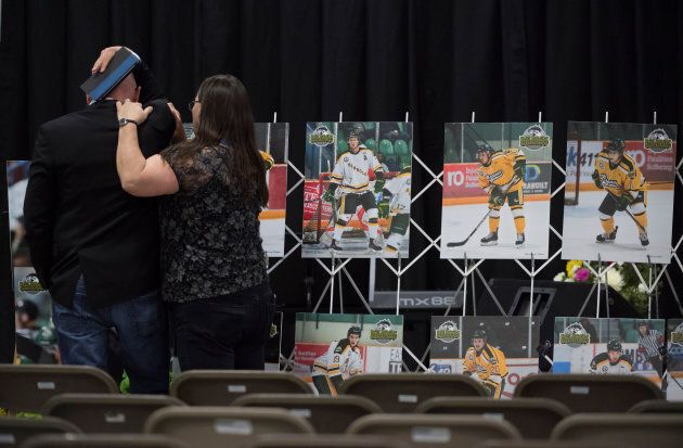 A man is comforted as he looks at photographs before a vigil at the Elgar Petersen Arena, home of the Humboldt Broncos, to honour the victims of a fatal bus accident in Humboldt, Sask. on April 8, 2018.