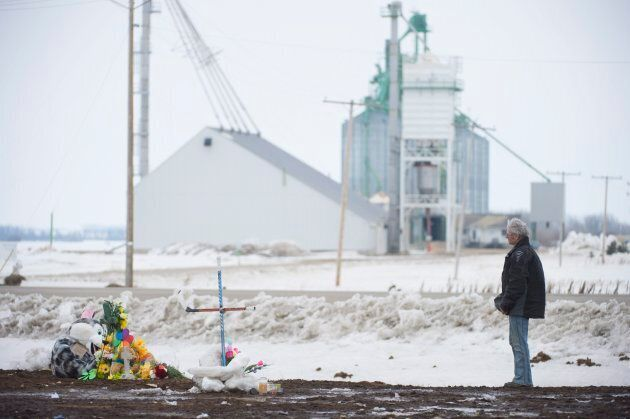 A man pays his respects at a make shift memorial at the intersection of a fatal bus crash near Tisdale, Sask. on April, 9, 2018.