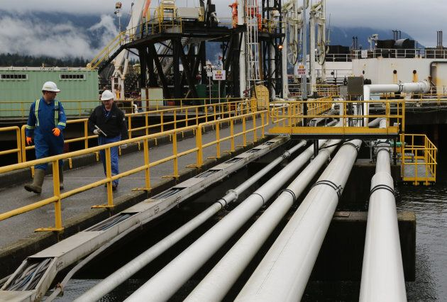Workers walk to a jet fuel barge at Kinder Morgan's Westridge Terminal on Burrard Inlet in Burnaby, B.C.,...
