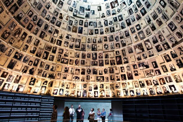 Visitors look at pictures of Jews killed in the Holocaust during a visit to the Hall of Names at Yad...