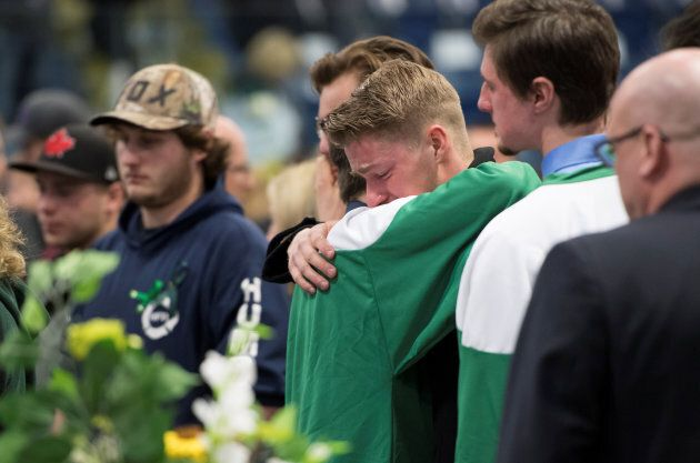 Mourners comfort each other during a vigil at the Elgar Petersen Arena, home of the Humboldt Broncos,...