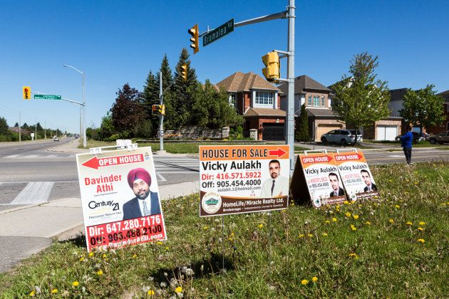 Open house signs displayed on the side of a road in Brampton, Ont., Sat. May 20, 2017. The slowdown in...