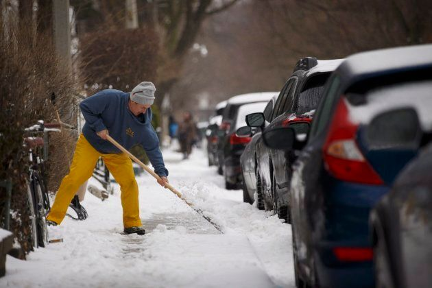 Stefan Randstrom clears ice from his sidewalk in Toronto as a mix of snow, hail, and rain fall on April...
