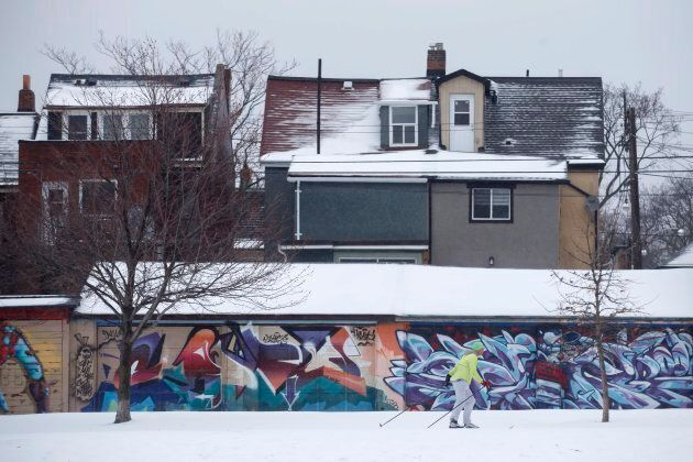 A man skis past houses on the edge of Trinity Bellwoods Park in Toronto as a mix of snow, hail, and rain...