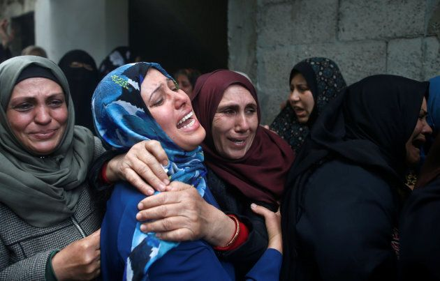 Relatives of Hamdan Abu Amshah, who was killed along Gaza's border with Israel, mourn during his funeral...