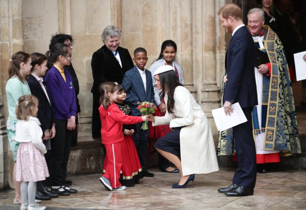 Meghan Markle and Prince Harry talking to children as they leave the Commonwealth Service at Westminster...