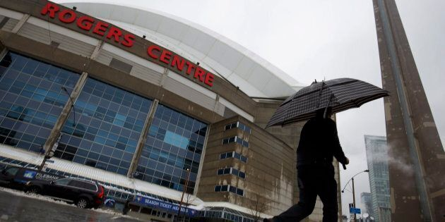 A man walks by the Rogers Centre as reports of falling ice from the CN Tower sparked a closure of parts...