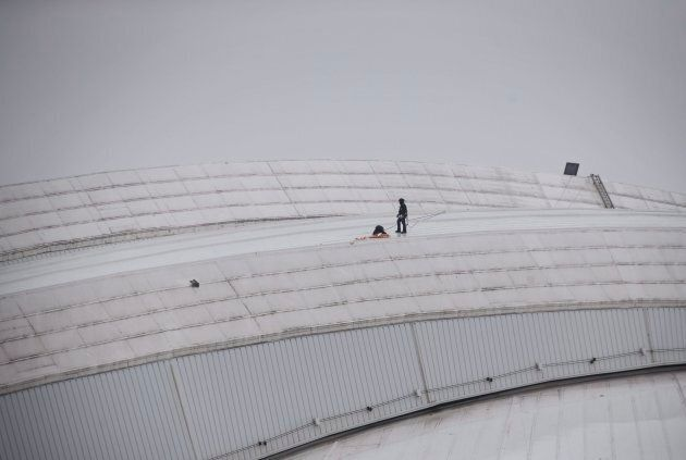 Workers examine a hole in top of the Rogers Centre as the area around the CN Tower is closed off due...