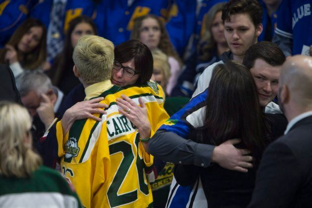 Attendants hug during the funeral of Humboldt Broncos player Evan Thomas in Saskatoon, Sask., on April,...