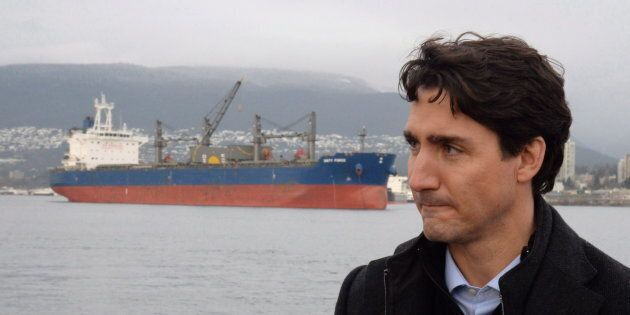 A freighter is seen in the background as Prime Minister Justin Trudeau tours a tugboat in Vancouver Harbour,...