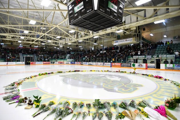 Flowers lie on the ice as people gather for a vigil on April 8 at the Elgar Petersen Arena, in Humboldt,...