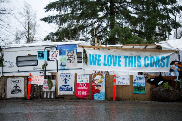 Protest signs are displayed outside of the Kinder Morgan Inc. facility in Burnaby, B.C. on April 11,