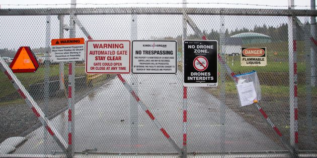 Warning signs are displayed on a fence outside of the Kinder Morgan Inc. facility in Burnaby, B.C., Wed....