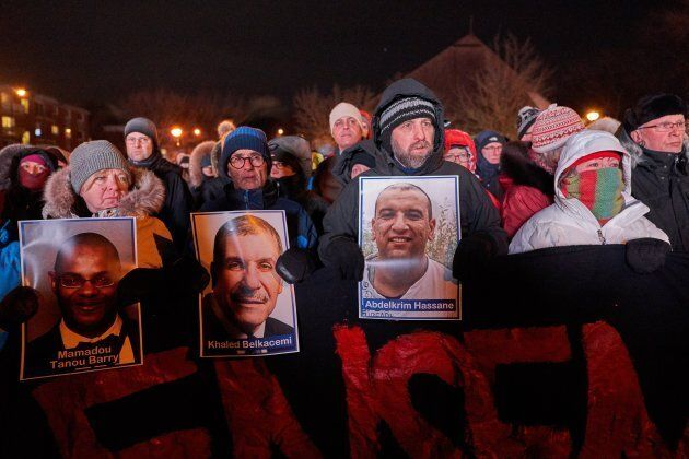 People hold pictures of victims while attending a vigil for the victims of the Islamic Cultural Centre...