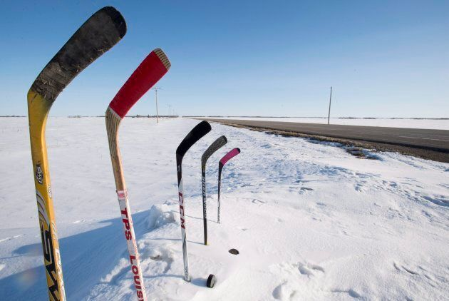 Hockey sticks to remember members of the Humboldt are seen standing in a snowbank along a stretch of...