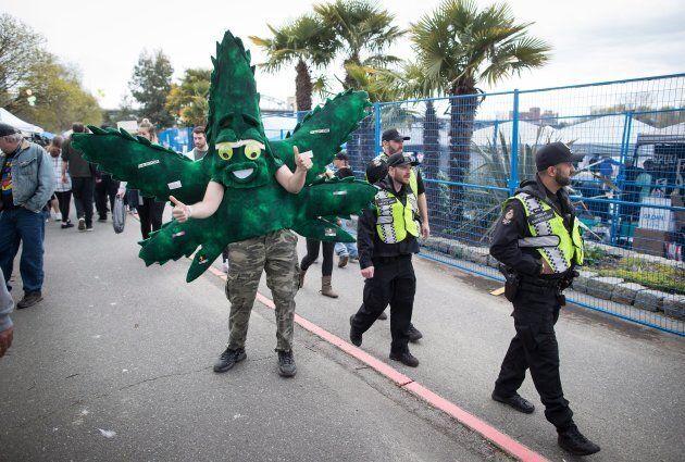 Police officers walk past a man wearing a marijuana leaf mascot costume during the 4-20 annual marijuana...