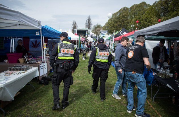 Police officers walk between tents setup by vendors at Sunset Beach during the 4-20 annual marijuana...