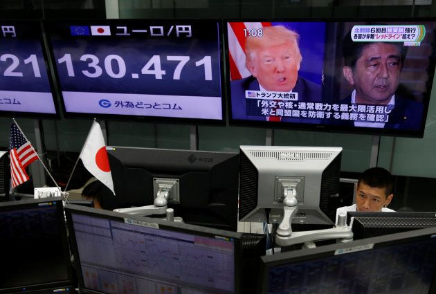 An employee of a foreign exchange trading company works near a monitor showing Japan's Prime Minister Shinzo Abe, right, and U.S. President Donald Trump, left, in a television news report.