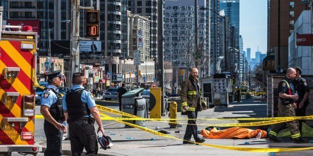 A body lies covered on the sidewalk in Toronto after a van mounted a sidewalk, crashing into a number...
