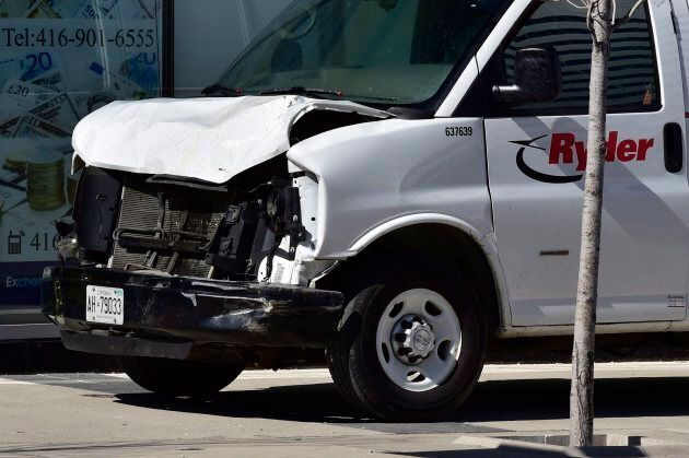 A van with a damaged front-end is shown on a sidewalk after a vehicle mounted a sidewalk crashing into...