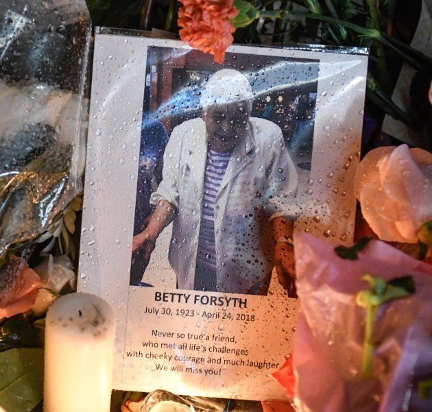 A photo of Betty Forsyth is shown at a vigil on Yonge Street in
