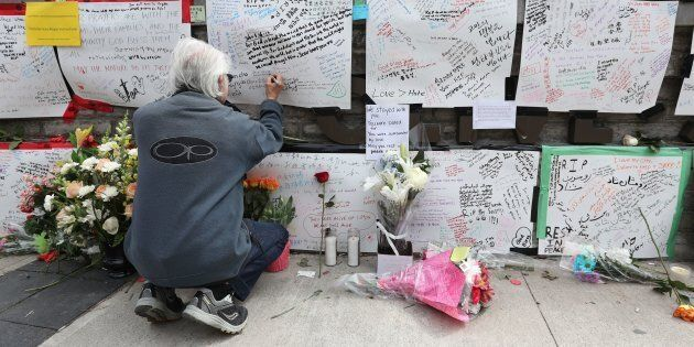 Jack Young leaves a note on a makeshift memorial for victims in the van attack in Toronto on April 24,