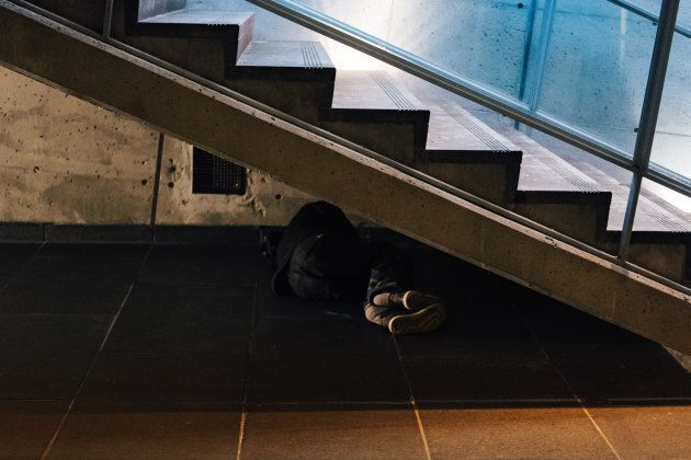 A man sleeping under the stairs at Square Victoria metro station, Montreal,