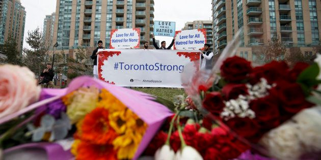 A local Toronto Muslim group holds up signs for love and courage for victims of the April 23 crash, at...