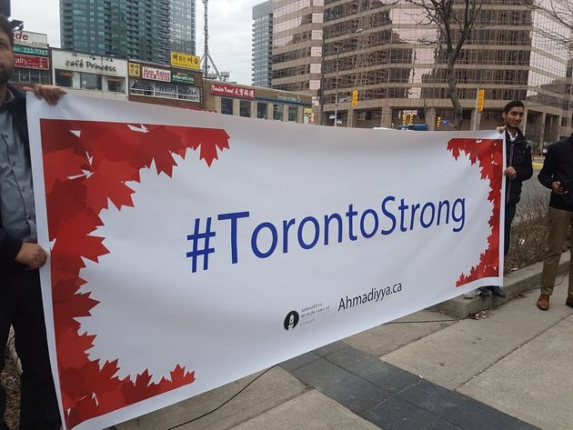A banner from Ahmadiyya Muslim Jama'at Canada is held up at a memorial at Yonge Street near Finch Avenue...