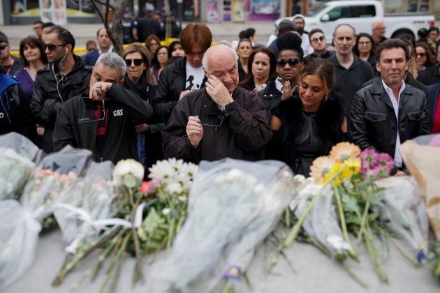 People gather for a moment of silence at a memorial for victims of the mass killing on Yonge St. at Finch...