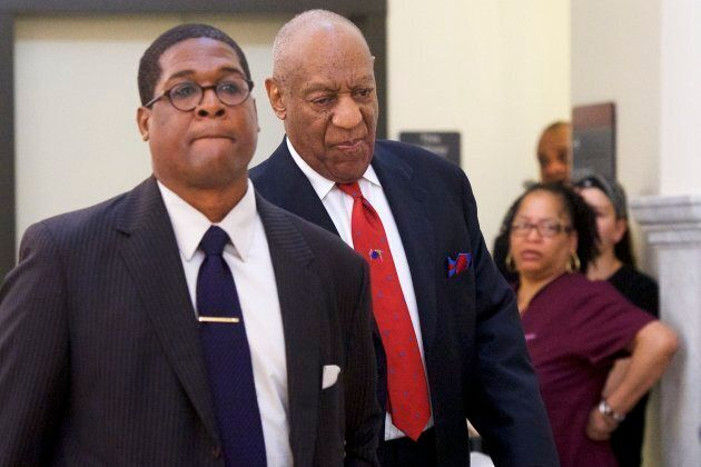 Bill Cosby, centre, walks through the Montgomery County Courthouse with his publicist, Andrew Wyatt,...