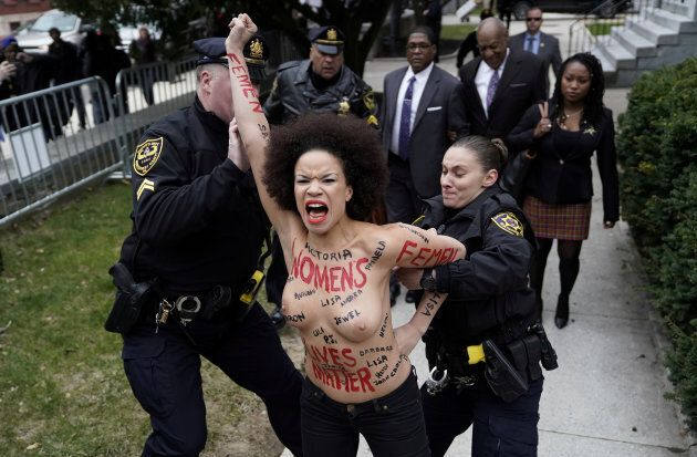 Protester Nicolle Rochelle is subdued by the police after breaking through the barriers, as actor and comedian Bill Cosby arrives for the first day of his sexual assault retrial at the Montgomery County Courthouse in Norristown, Pennsylvania, April 9, 2018.