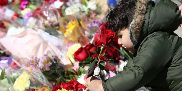 A boy leaves a rose at a memorial in Mel Lastman Square ahead of a vigil for the van attack victims,...