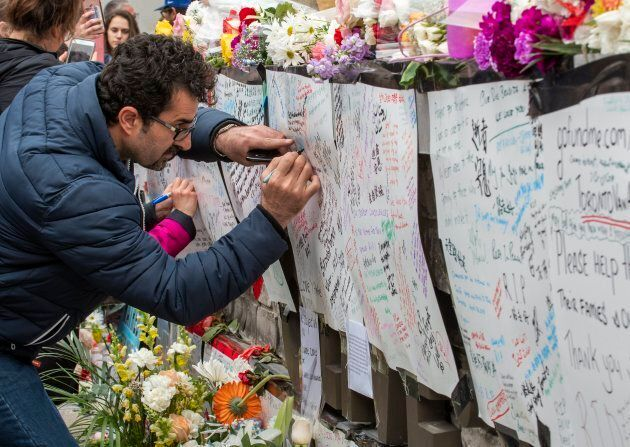 A man writes a message at a makeshift memorial across the street from where a man in a rented van plowed...