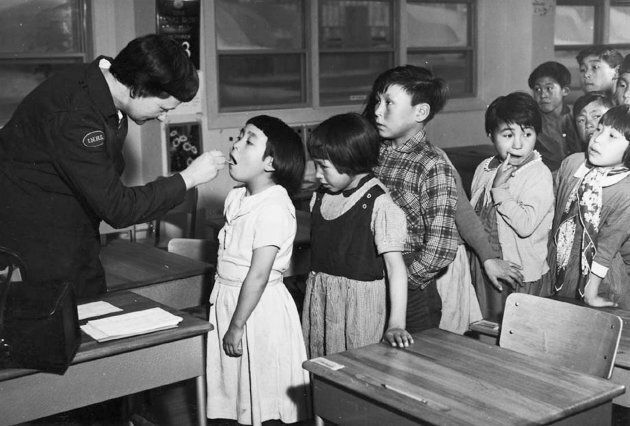 A nurse checking a girl's throat at the segregated Frobisher Bay Federal Hospital in Iqaluit, Nunavut, in a 1959 archive photo.