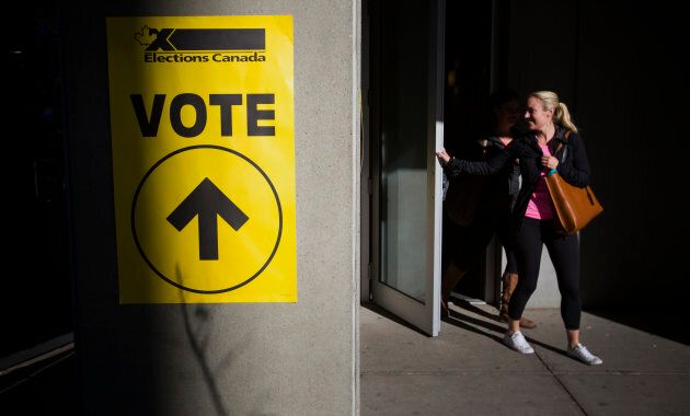 People exit a voting station on election day in Calgary, Alta. on Oct. 19,